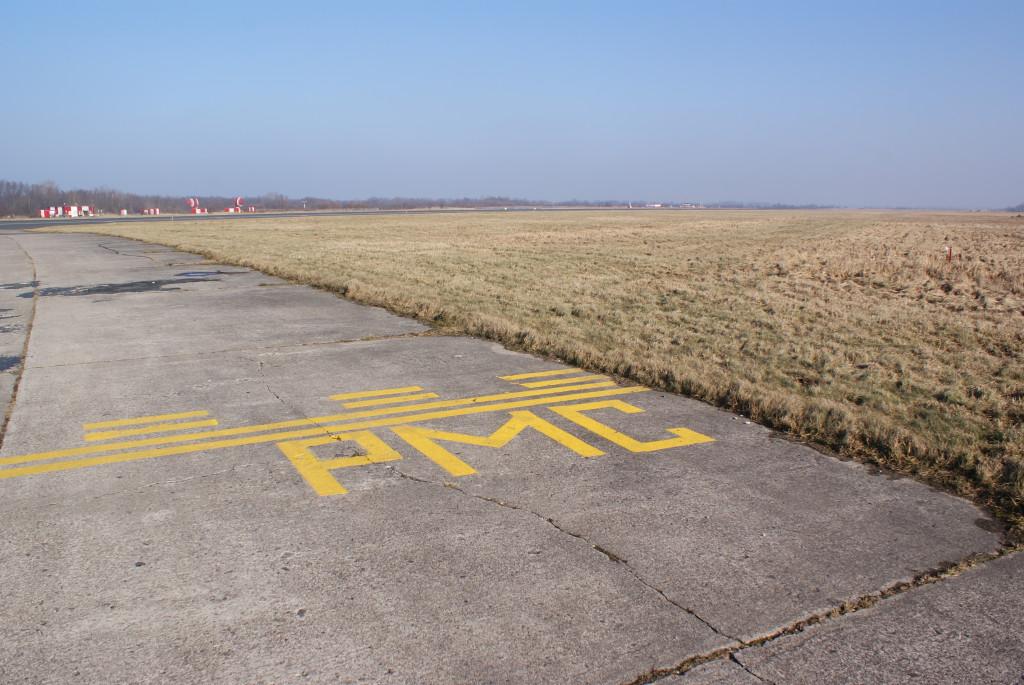 РМС значит радиомаячная система. Возле полосы расположены курсовой и глиссадный маяки системы ILS, с помощью которой осуществляется точный заход на посадку. Любой объект, который окажется между маяком и самолетом, внесет существенные искажения в работу системы и посадку придется прервать. Поэтому пересекать желтую линию можно только тогда, когда самолеты на посадку не заходят.
