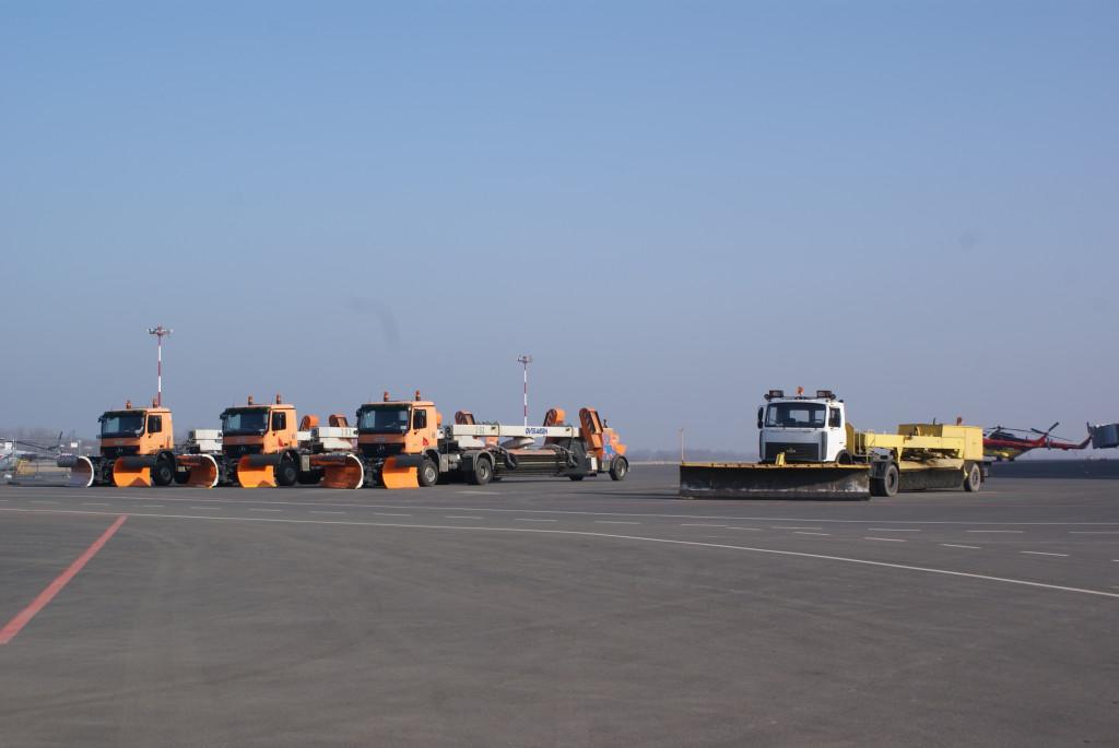 Машины-снегоуборщики чистят аэродром от снега. Правда, во время сильных снегопадов взлетно-посадочную полосу чистить бессмысленно, так как ее тут же заметает снова, а машин столько нет. В этом случае аэропорт просто временно закрывают. Во время чистки полосы она, естественно, тоже не работает: вылетающие рейсы задерживают, а прилетающие направляют в зоны ожидания — то есть, кружить неподалеку от аэропорта.