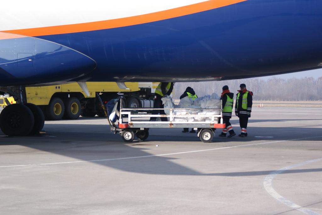Тележка используется для перевозки багажа. Сейчас мы видим, как в бомболюк грузят мешки с песком: их сбрасывают по мере набора высоты для снижения веса самолета. (На самом деле это, конечно, просто принятый к перевозке груз помимо багажа пассажиров. Да-да, груз летает не только на грузовых самолетах). За самолетом виднеется топливозаправщик.